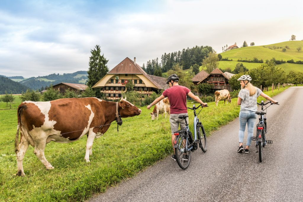 Schweiz. ganz natuerlich. eBiker Paar mit Kuehen vor einem traditionellen Emmentaler Bauernhaus.  Switzerland. get natural.  eBiker couple with cows in front of a traditional Emmental farmhouse.  Suisse. tout naturellement.  Couple d'eBiker avec des vaches devant une ferme traditionnelle de l'Emmental.  Copyright by: Switzerland Tourism - By-Line: swiss-image.ch/Andre Meier