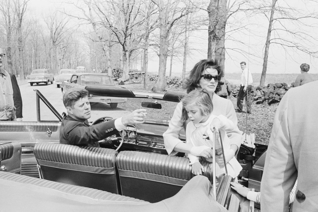 31 Mar 1963, Gettysburg, Pennsylvania, USA --- First Lady Jackie Kennedy holds up her daughter, Caroline, on a tour of Civil War battlefields in Pennsylvania. President Kennedy sits behind the wheel of the convertible. --- Image by © Bettmann/CORBIS