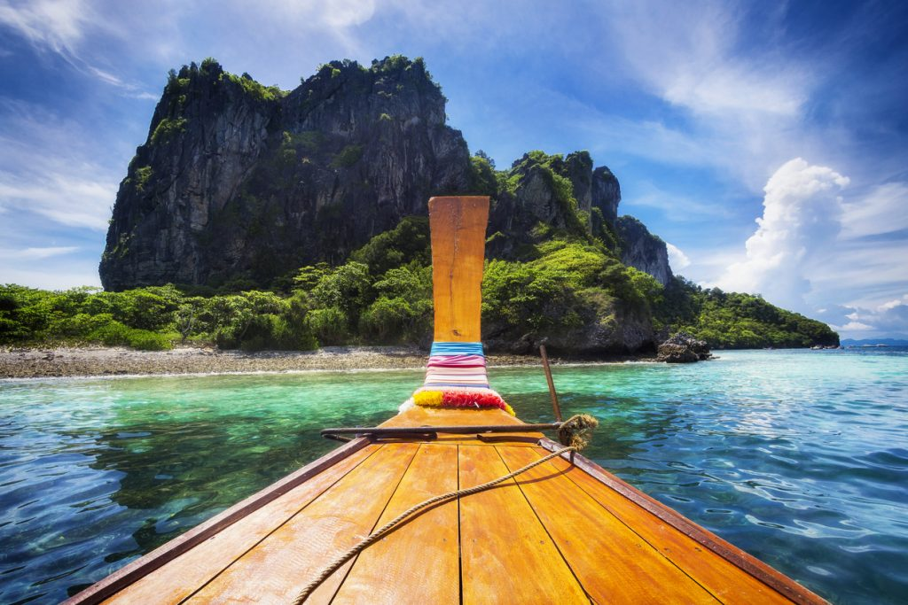 Traditional long tail boat on the way to famous Maya Bay beach in Koh Phi Phi Island, Krabi, Southern Thailand.