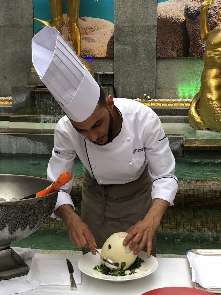 Lo chef Mohamed Lamnaour sbuccia un uovo sodo di struzzo
