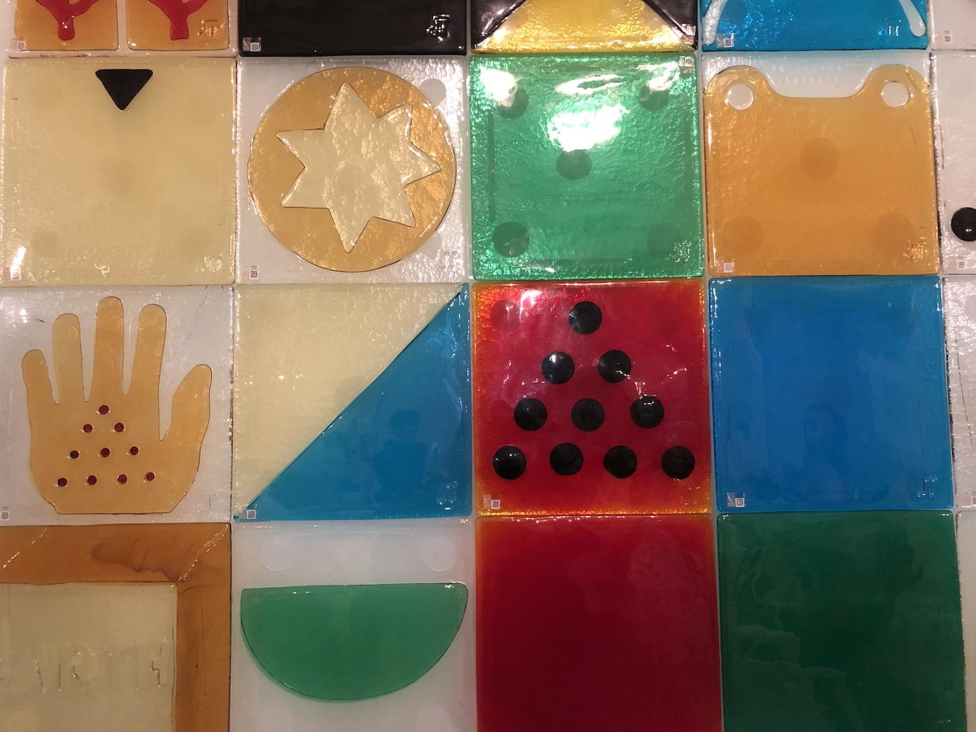 Particolare delle piastrelle in vetro ideate da Joe Tilson